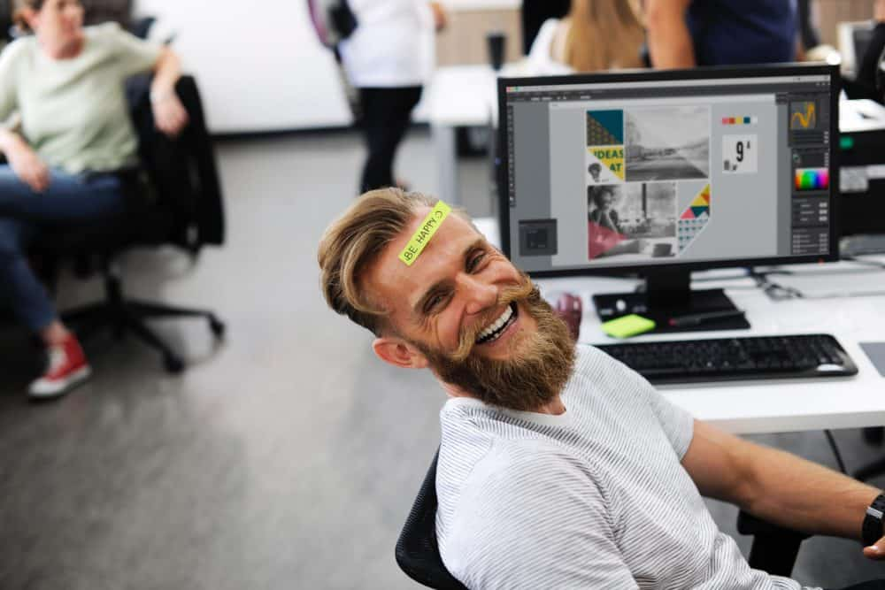 man laughing infront a computer