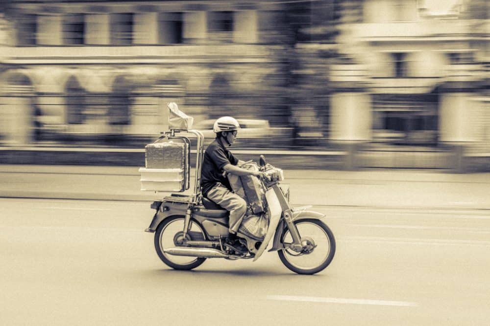 Delivery man speeding on a motorcycle